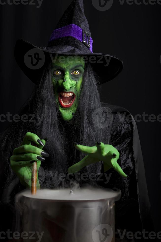 Scary witch stirring a smoky cauldron photo