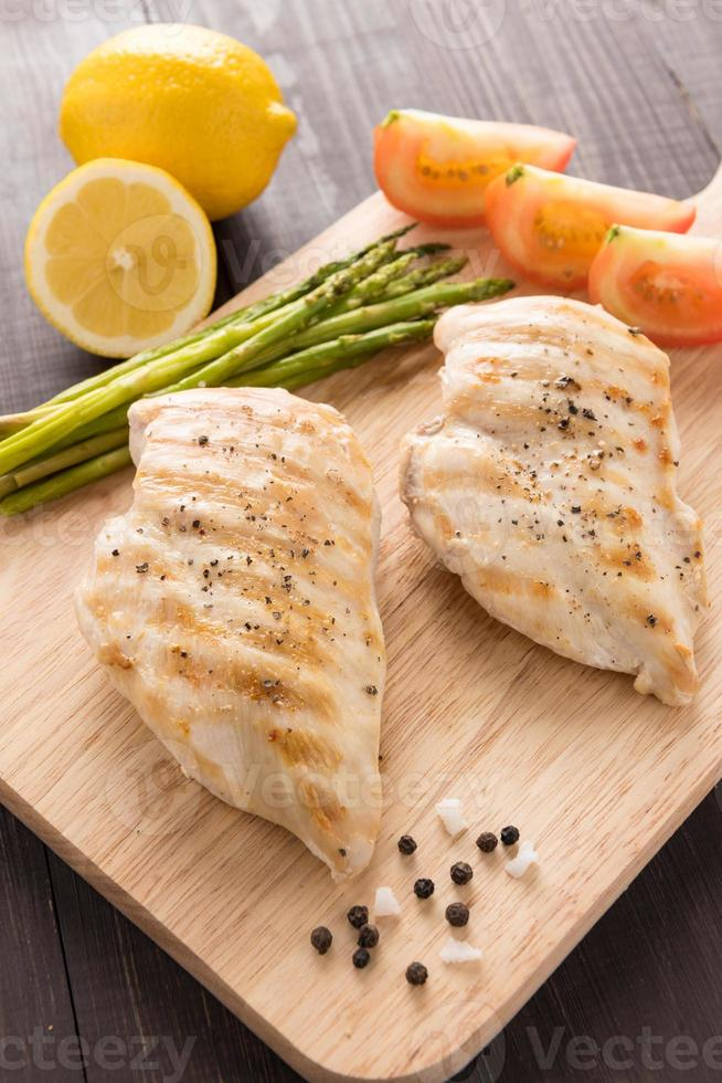 Marinated grilled chicken breasts on the wooden table photo