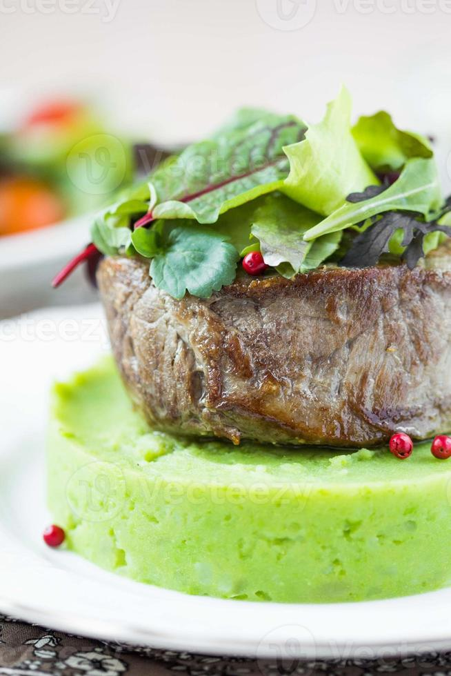 Grilled beef steak, green mashed potatoes with peas, herbs photo
