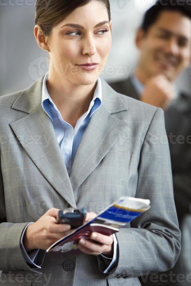 Empresaria en la terminal del aeropuerto, con teléfono y boleto foto