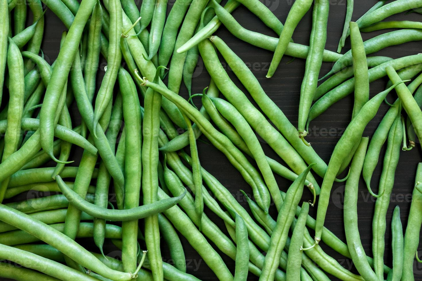 Whole French green string beans  on black rustic wood. photo