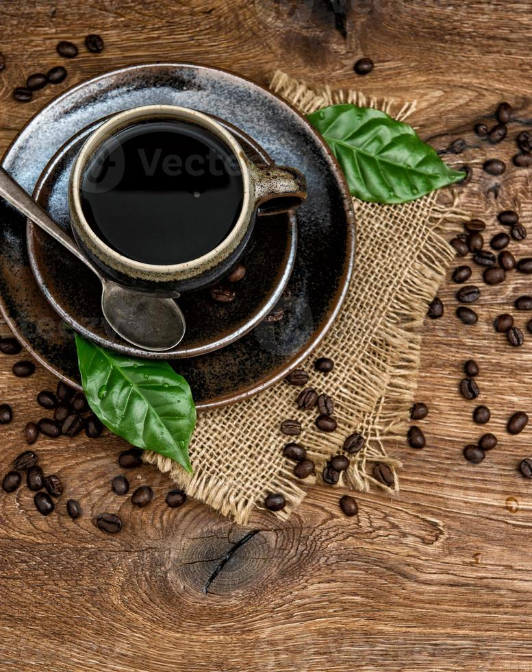 black coffee with beans and green leaves on wooden background photo