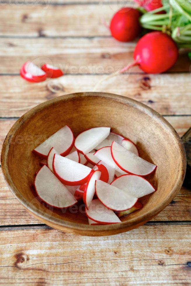 Sliced radishes  in a clay bowl photo