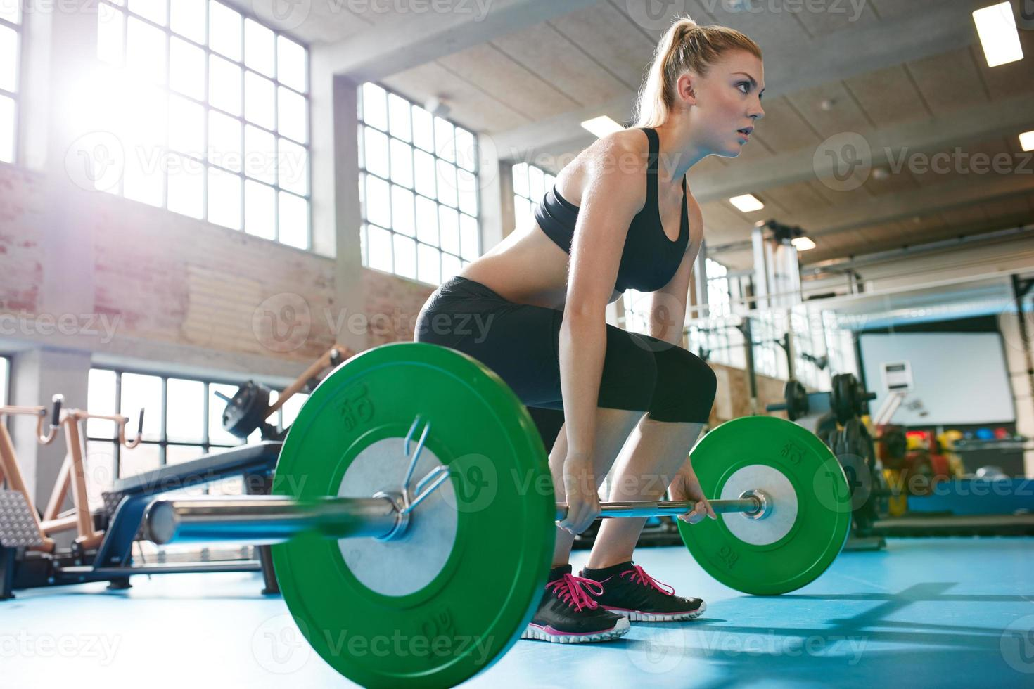 Woman in a gym doing heavy weight exercises photo
