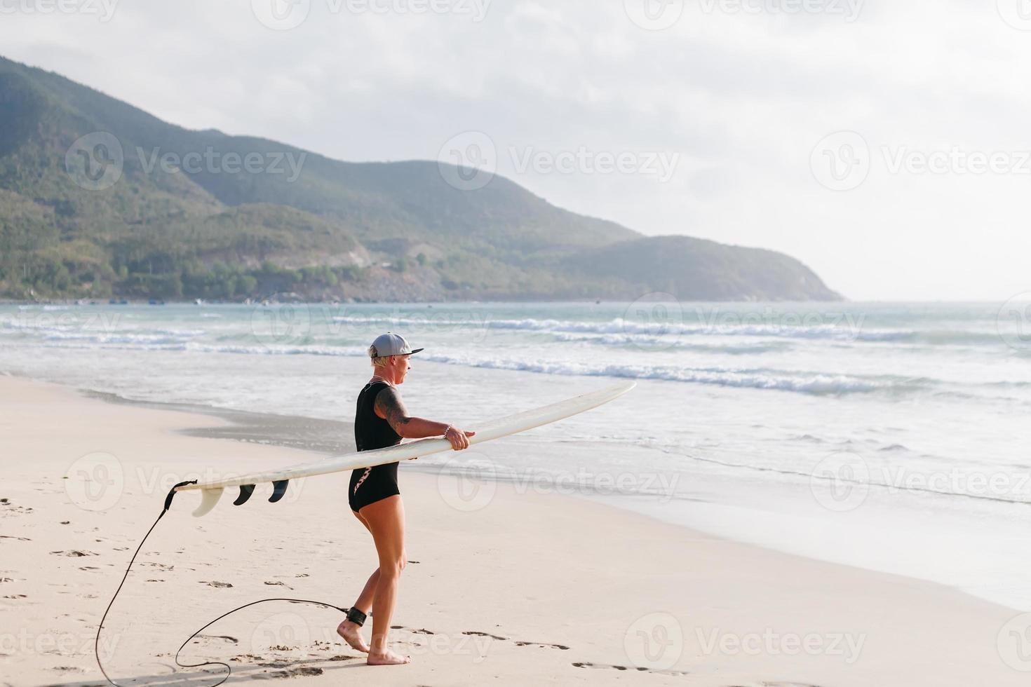 Mujer de surf con tabla de surf en la playa foto