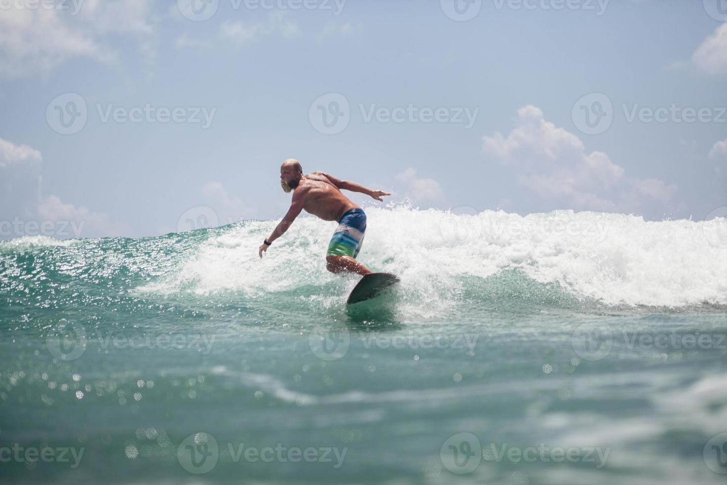 hombre surfista surfeando sobre las olas chapotean activamente foto