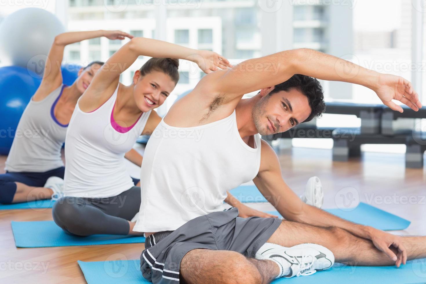gente deportiva estirando las manos en clase de yoga foto