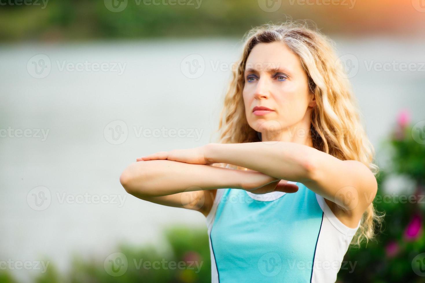 yoga. mujer joven haciendo ejercicio de yoga al aire libre foto