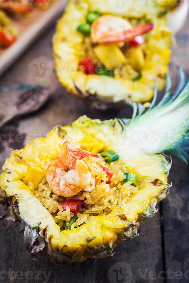 Pineapple fried rice shrimp on wooden table photo