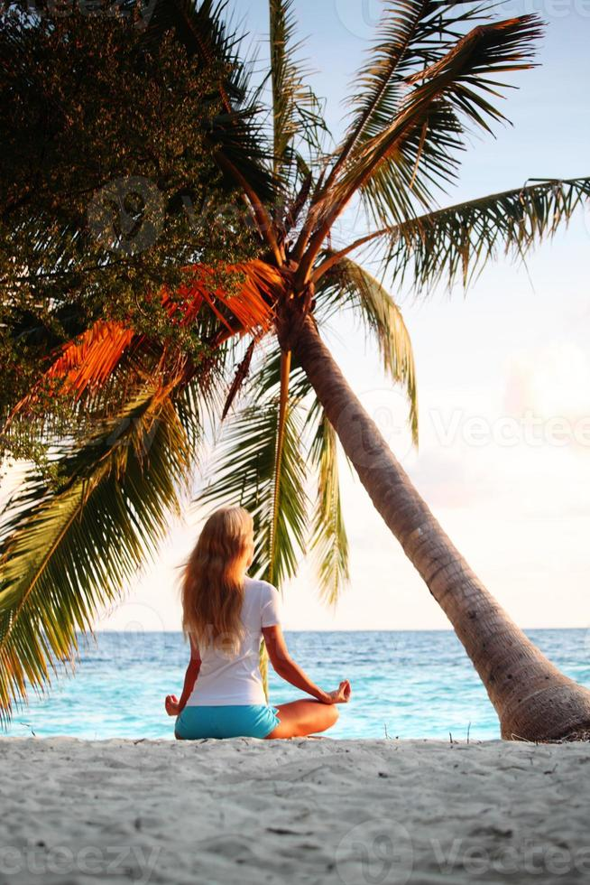 mujer de yoga bajo la palma foto