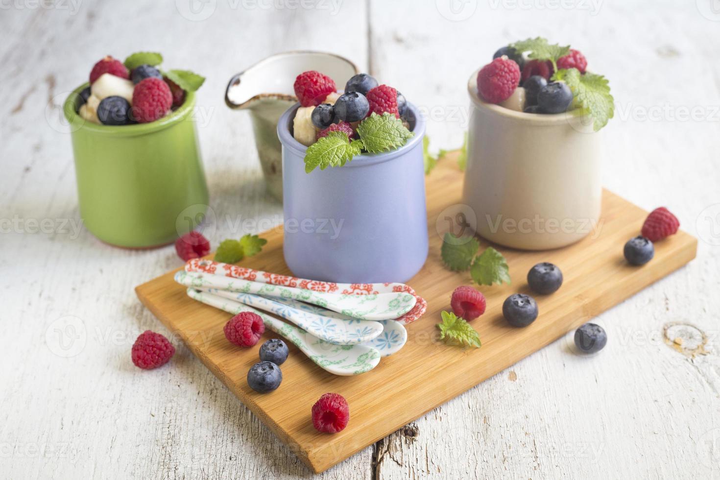 Ensalada de frutas con bayas frescas en platos a la carta foto