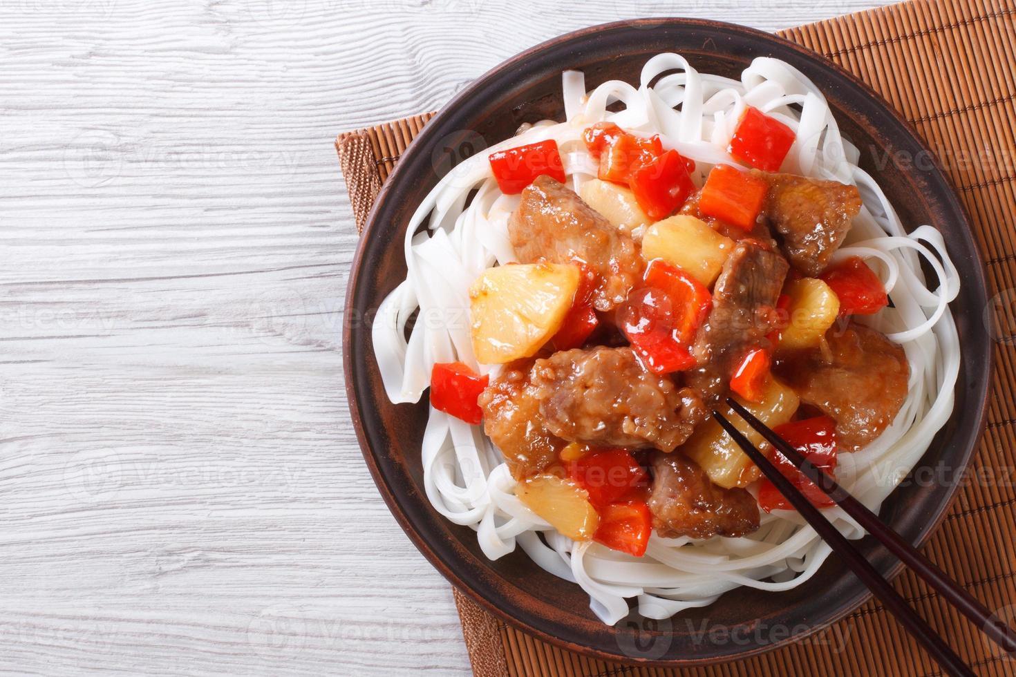 carne de porco em molho agridoce com vista superior de macarrão foto