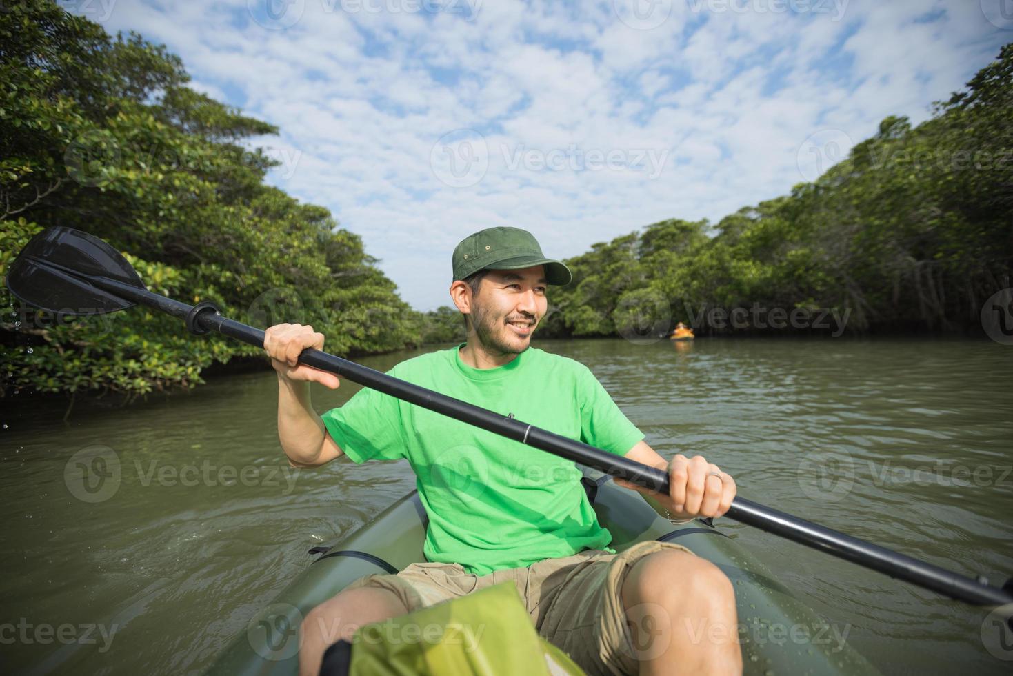 uomo che gode del kayak di fiume nella foresta di mangrovie, in Giappone foto