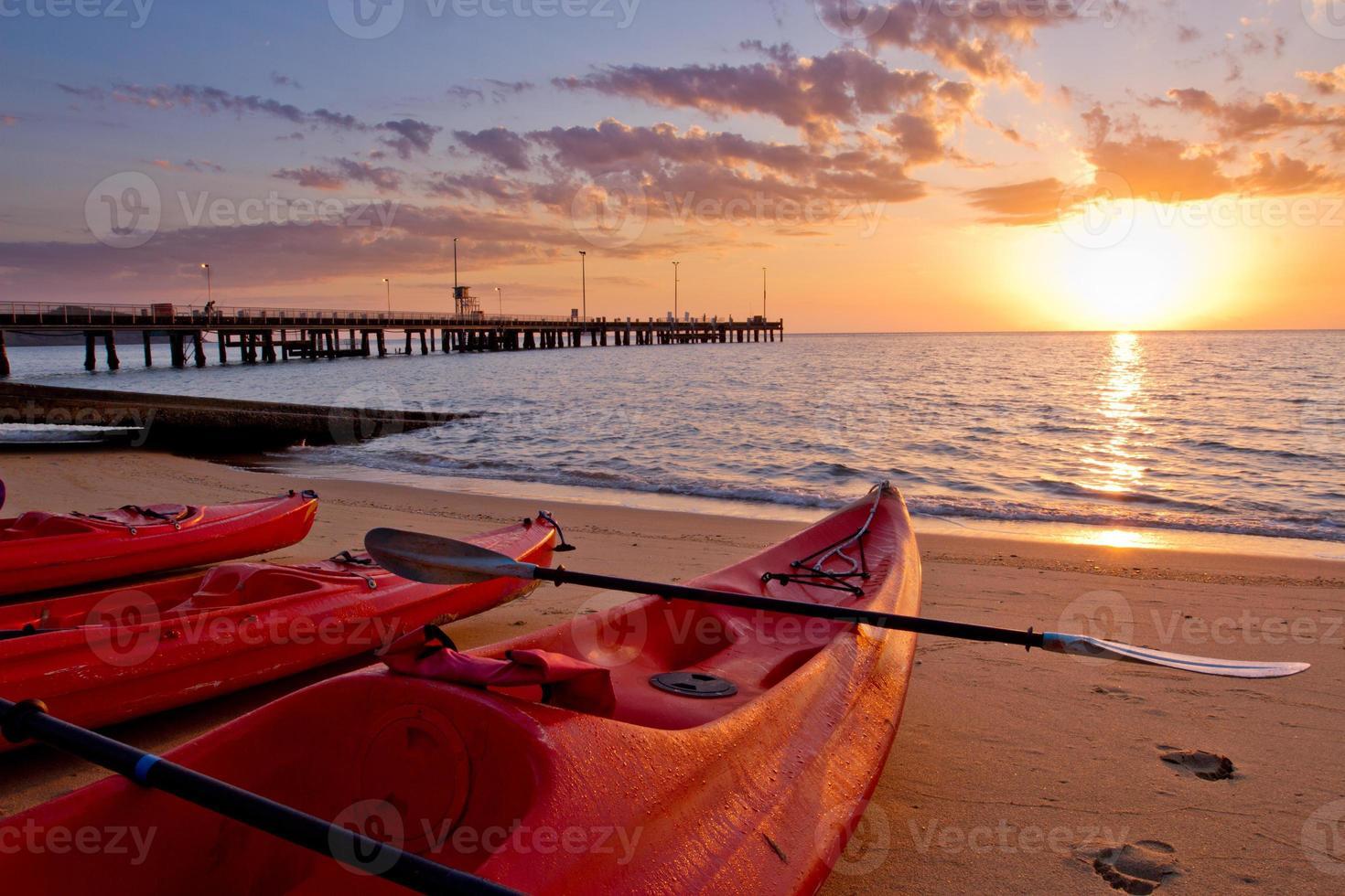 drie rode kajaks op het strand bij zonsopgang foto