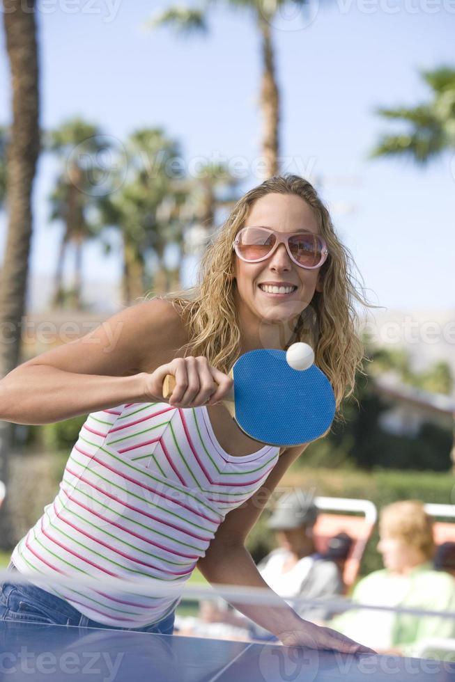 Hembra joven jugando tenis de mesa con personas en segundo plano. foto