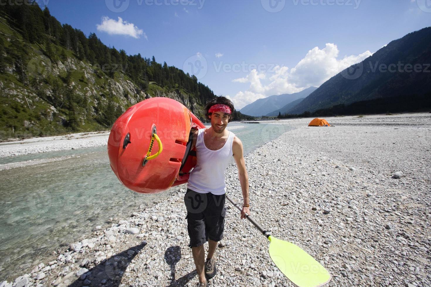 Alemania, Baviera, tierra de Tölzer, joven llevando remo de kayak sonriendo foto