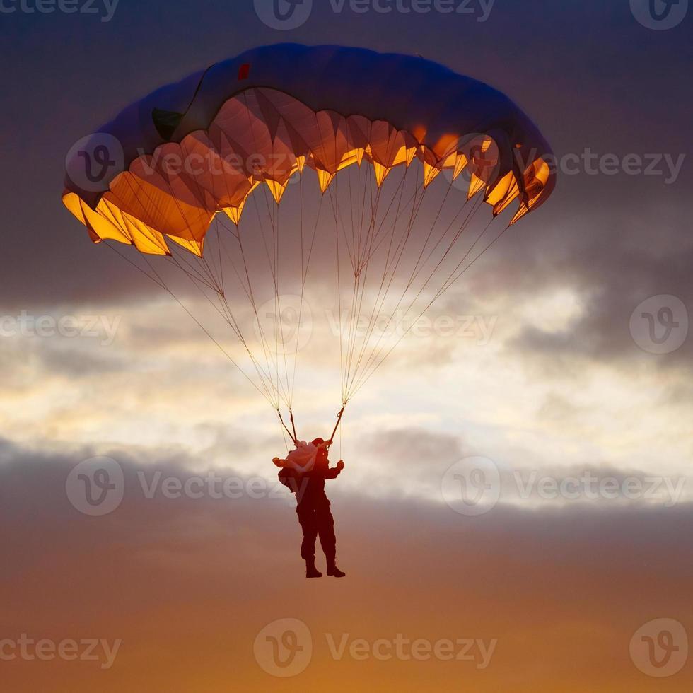 paracaidista en paracaídas colorido en cielo soleado foto