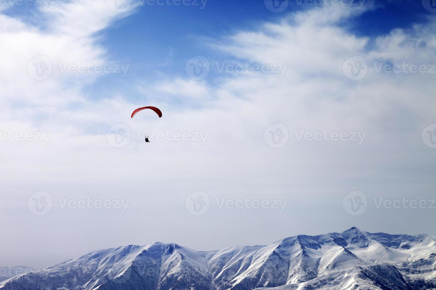 Paraglider silhouette of mountains in windy sky photo