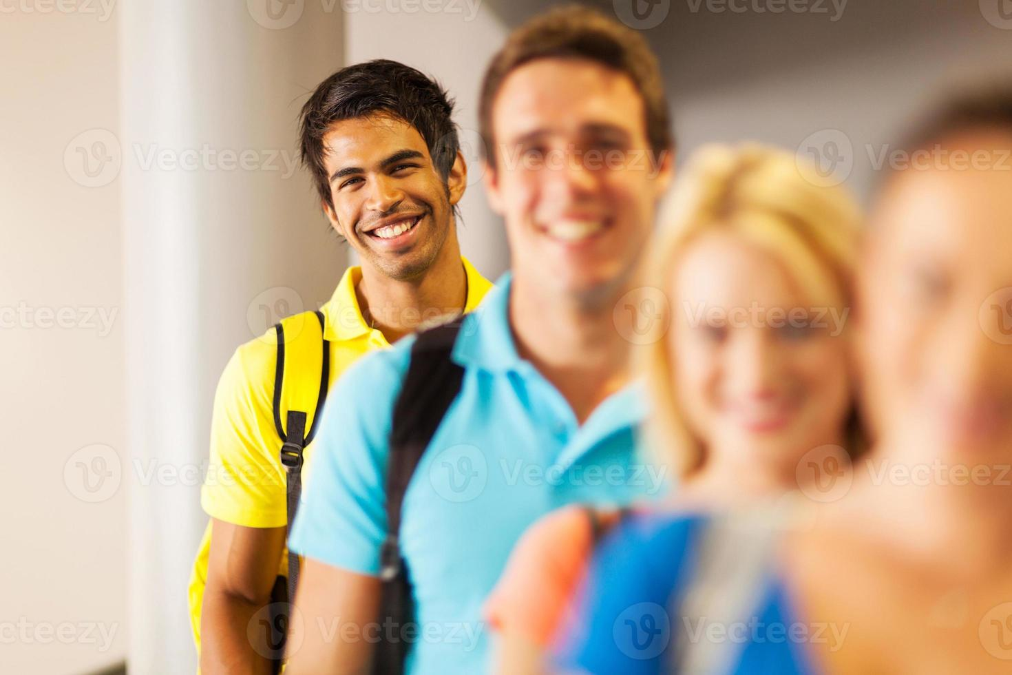 estudante do sexo masculino indiano em pé em uma linha foto