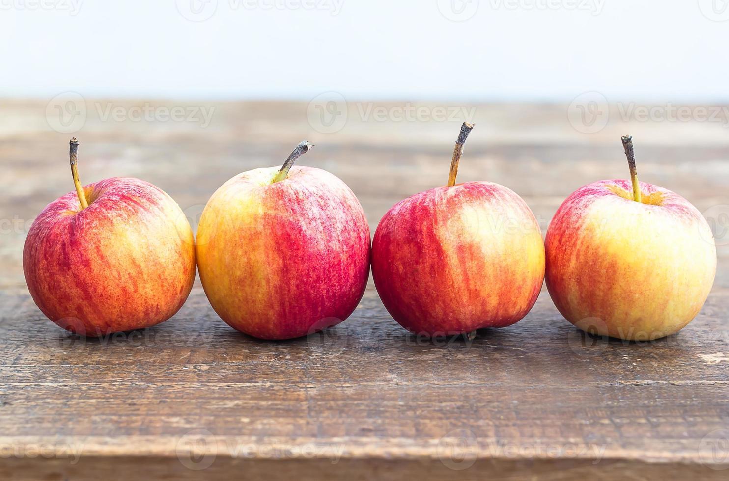 manzanas en fila en la mesa de madera foto