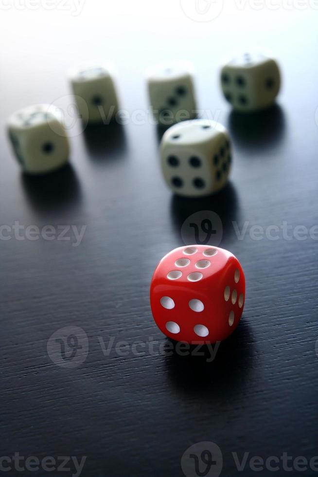 un dado rojo frente a cinco dados de juego blancos foto