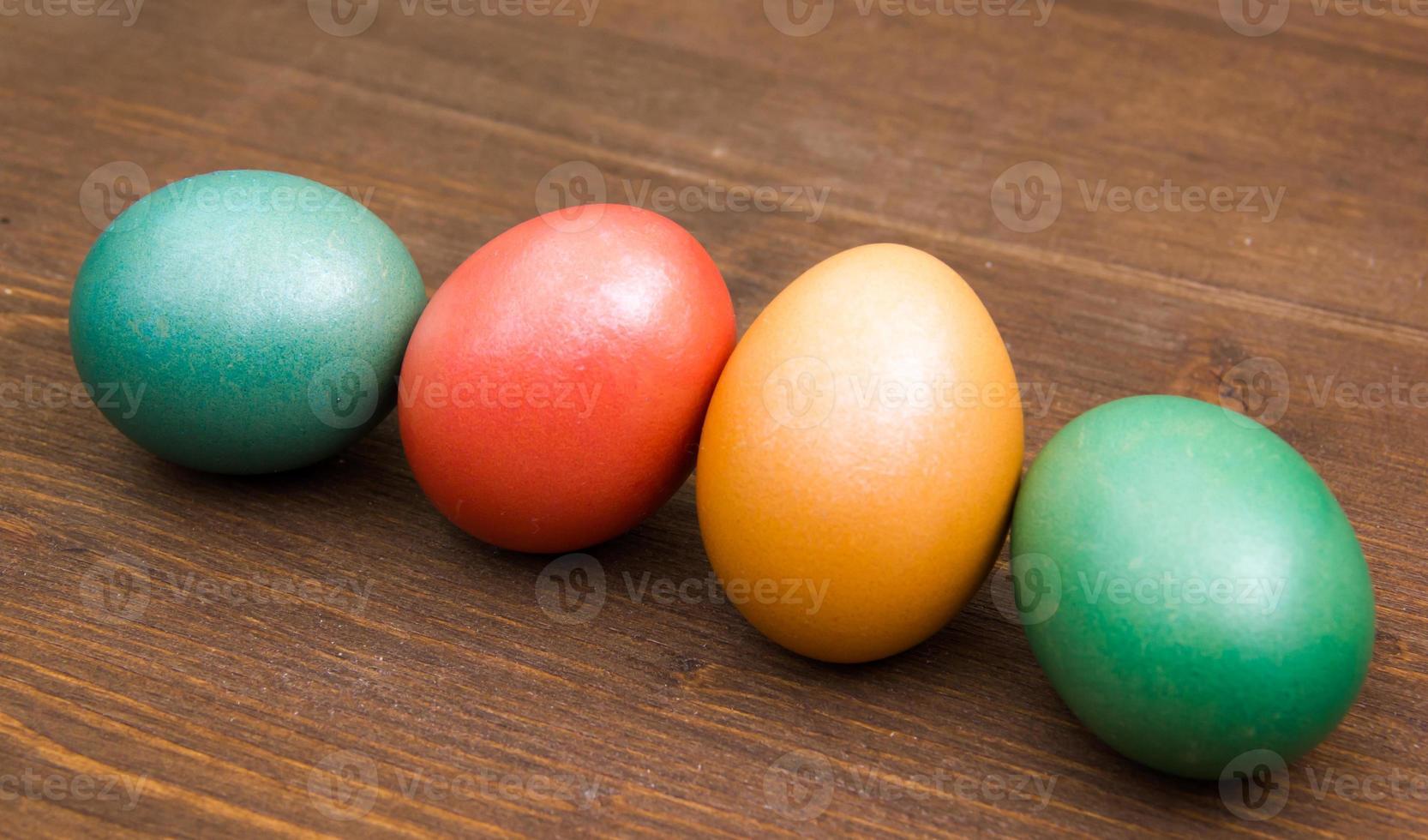 linha oblíqua de ovos coloridos na madeira foto