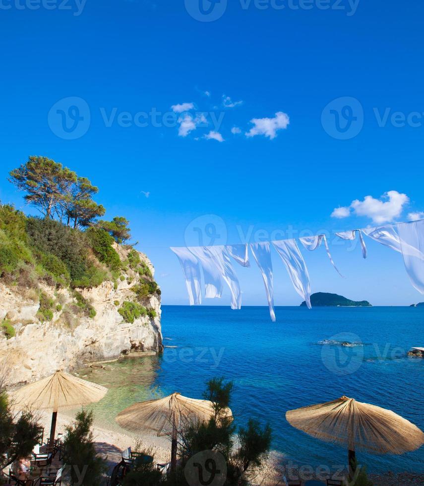 fila de sombrillas de paja y salones en la playa foto