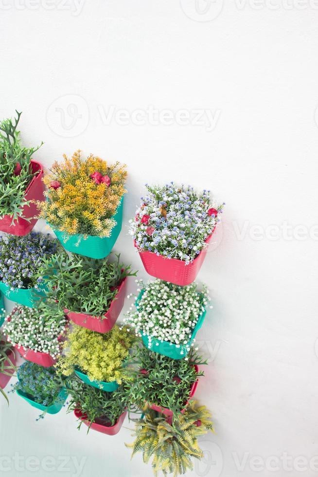 bloemen met kleurrijke plastic vaas hangen in de rij. foto