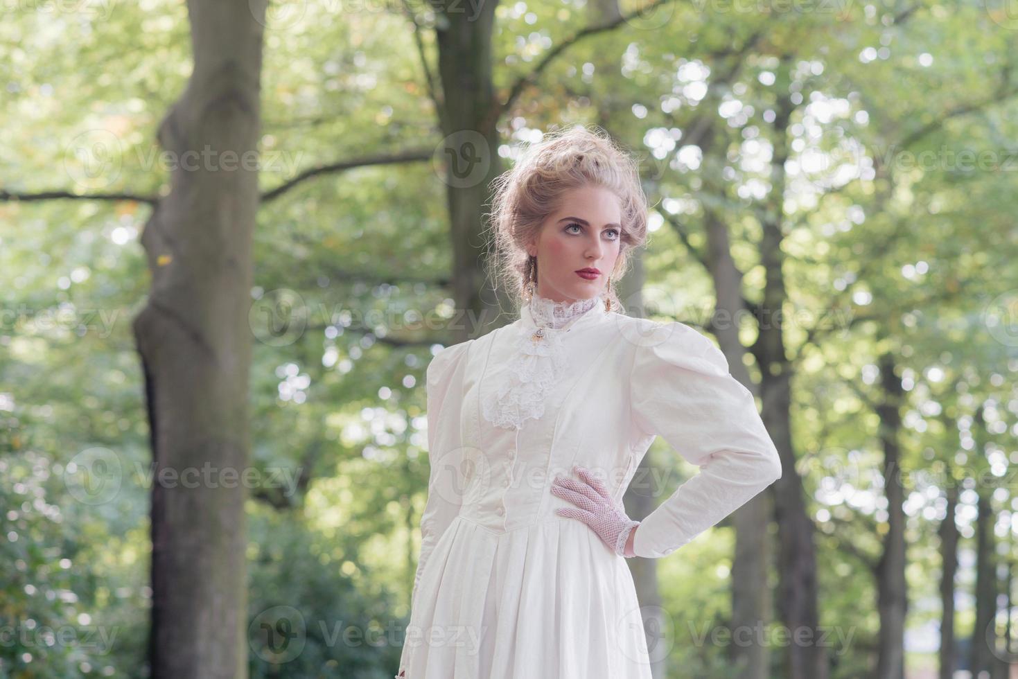 Retro mujer victoriana delante de la hilera de árboles. foto