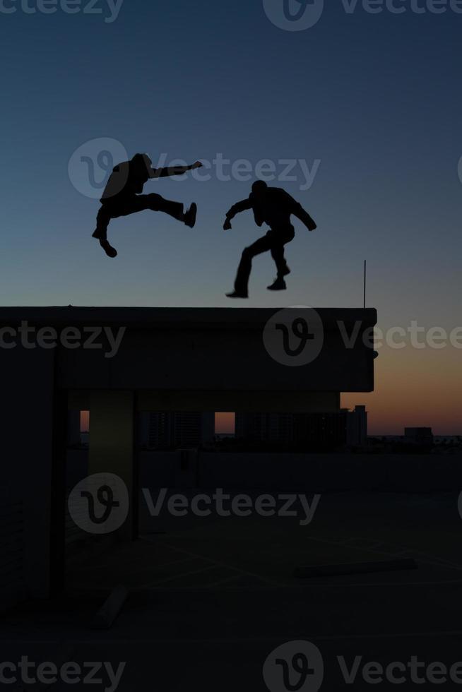 dois homens fazendo artes marciais no telhado foto