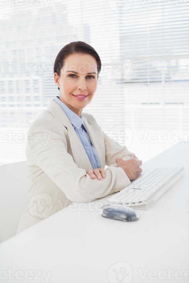 imprenditrice sorridendo alla sua scrivania foto