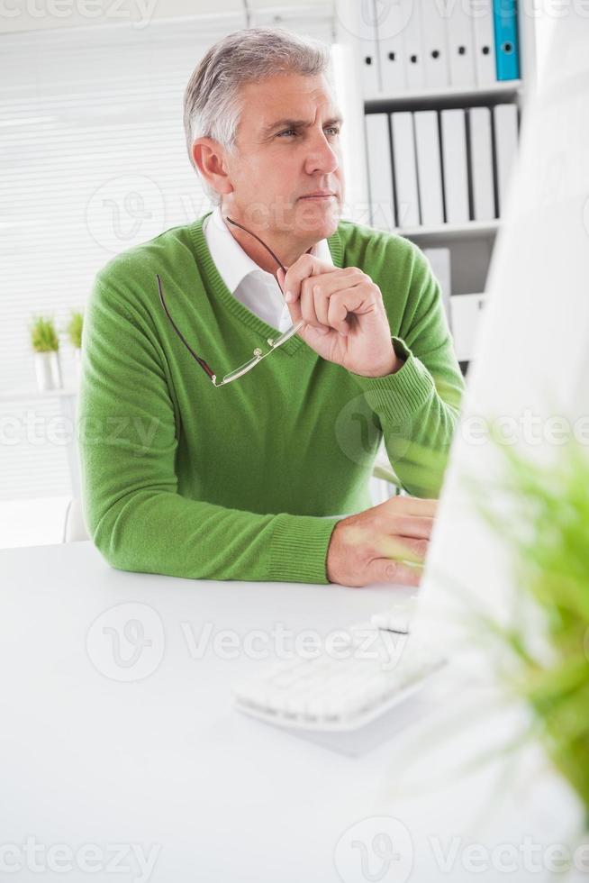 casual zakenman kijken naar computerscherm foto