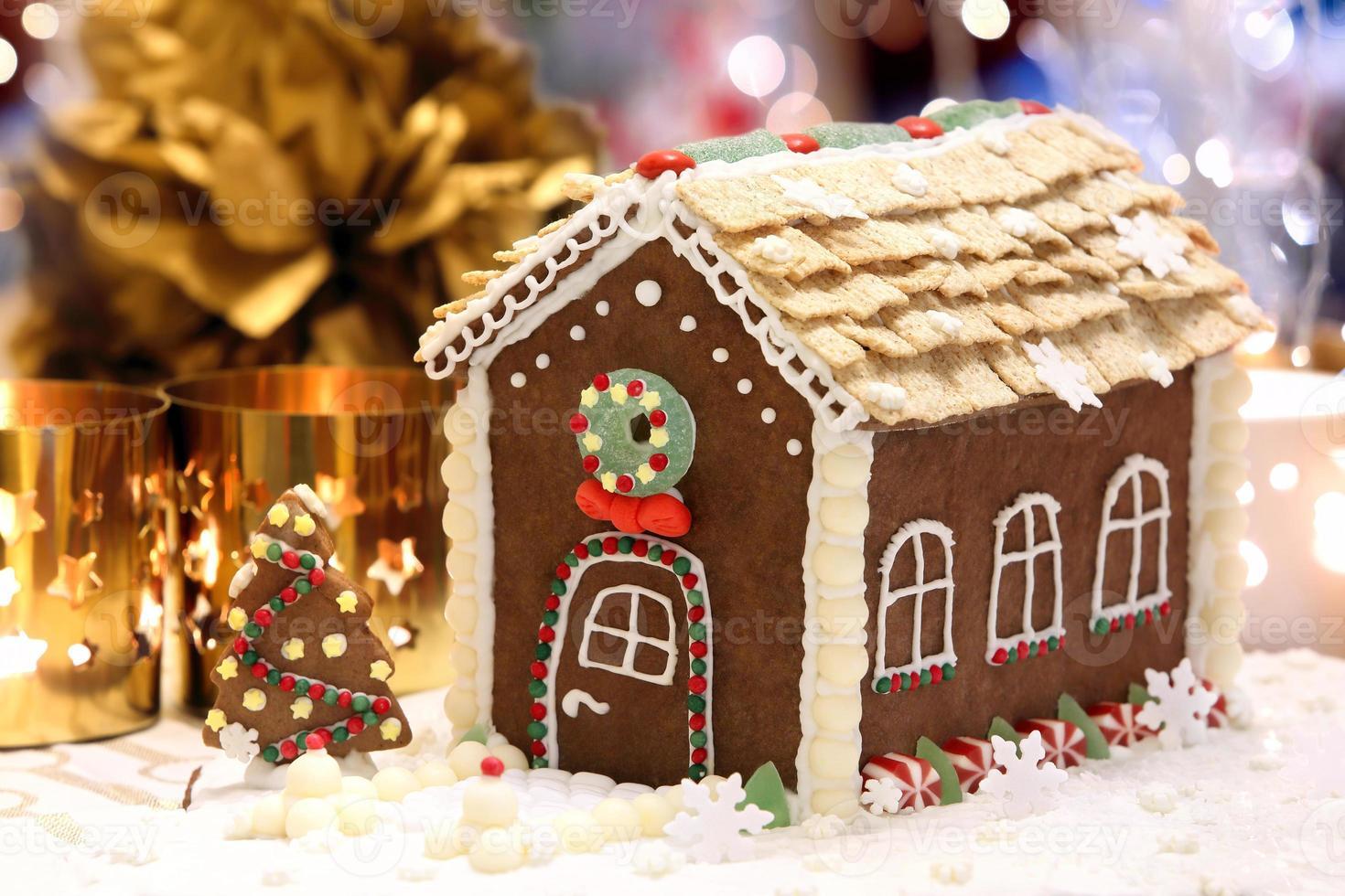 casa de pan de jengibre de navidad en la mesa decorada foto