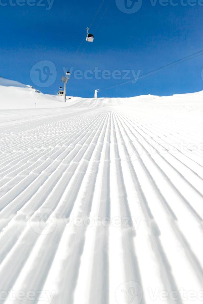 pista de esqui recém-preparado em um dia ensolarado foto