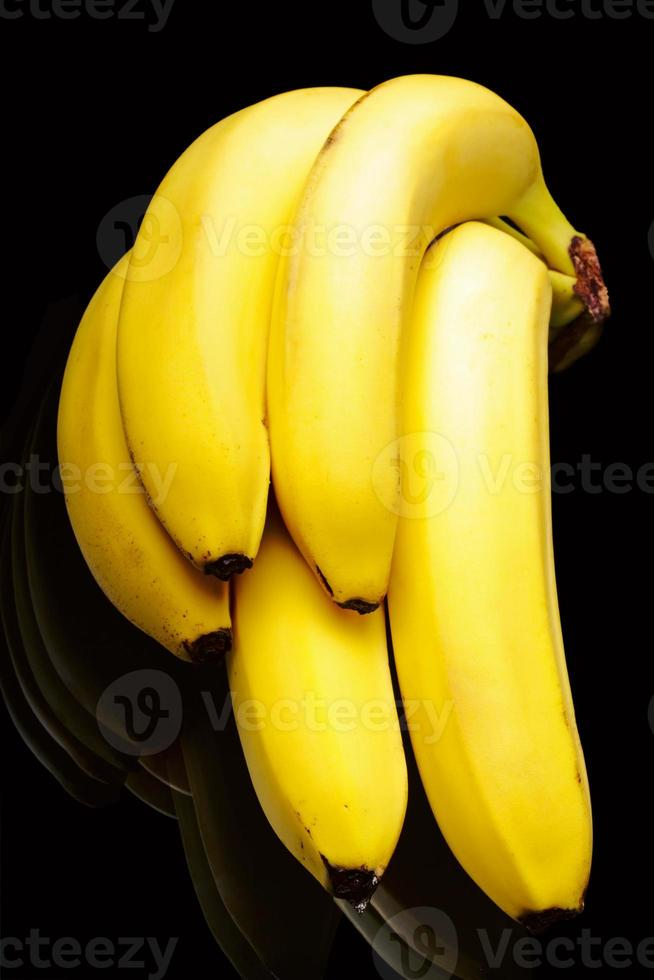 Bananas brunch on glass table. Black isolated. photo