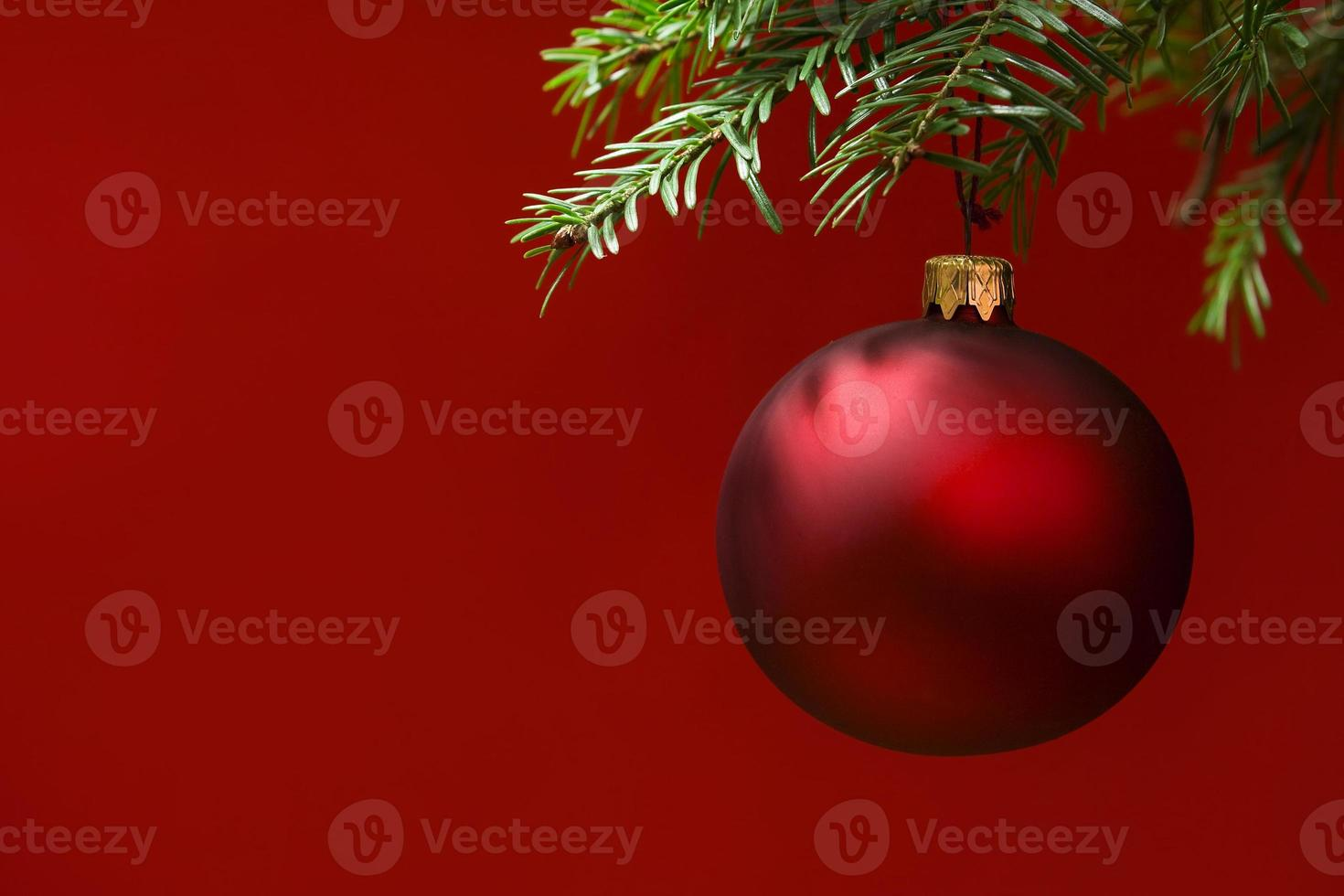 Tarjeta de Navidad con adornos de adorno rojo. fondo rojizo foto