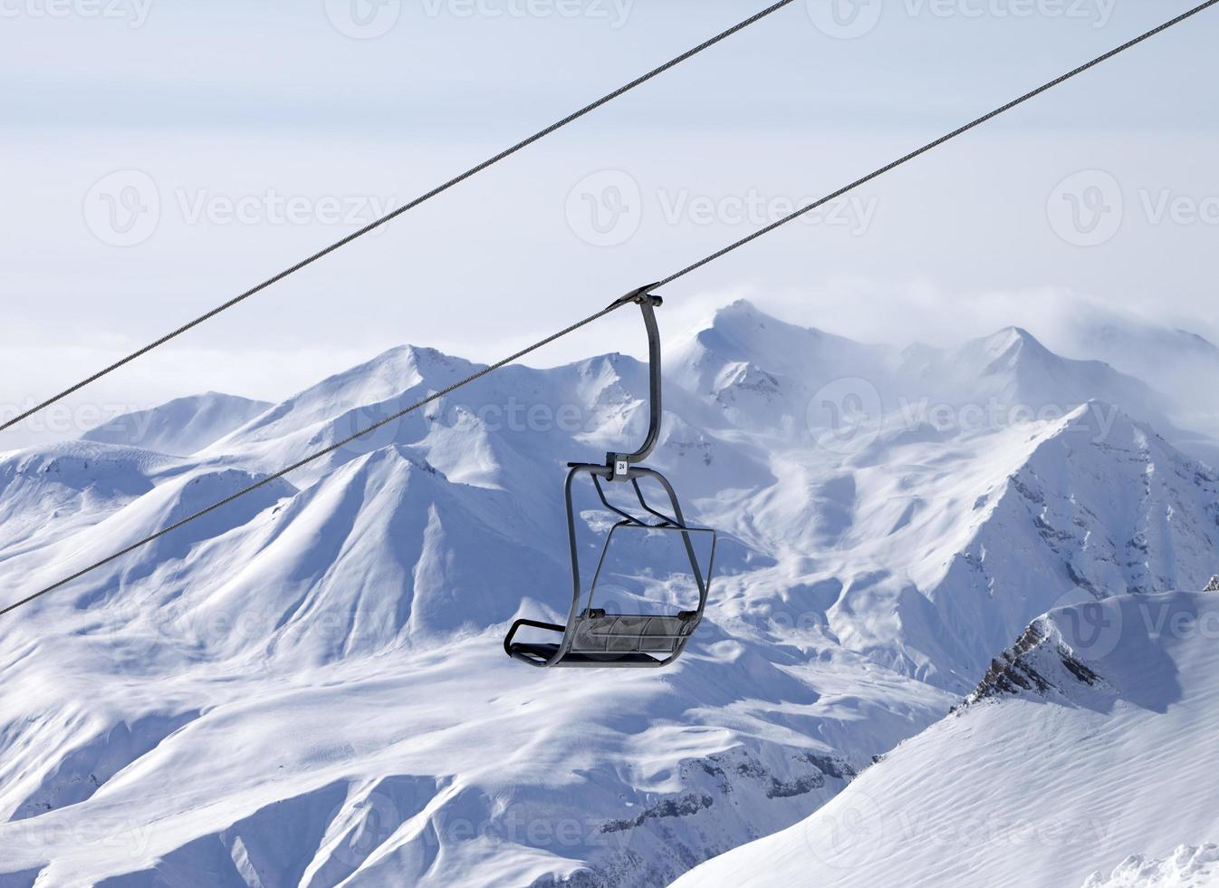 Chair lifts and off-piste slope in fog photo