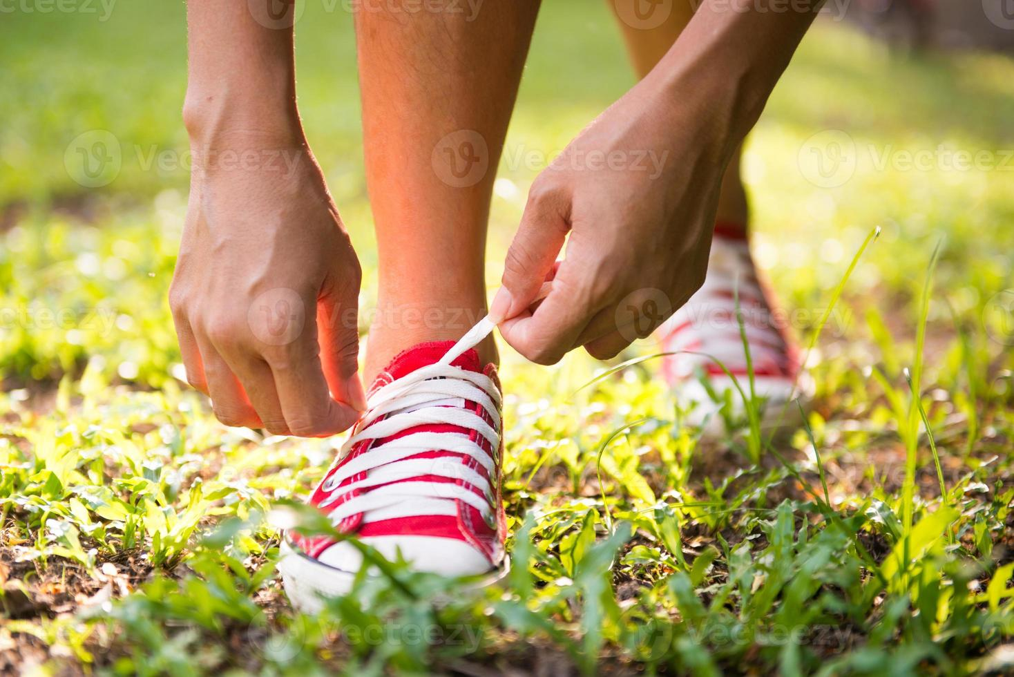 woman lacing her shoes before jogging in park photo
