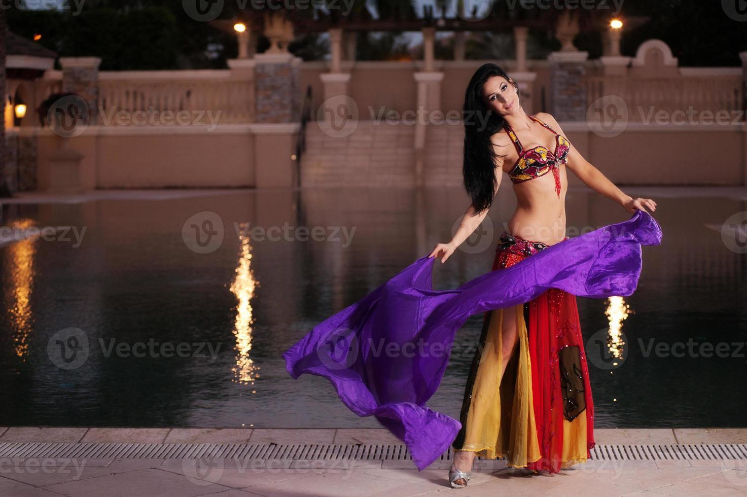 bailarina del vientre en traje rojo baila con velo morado foto