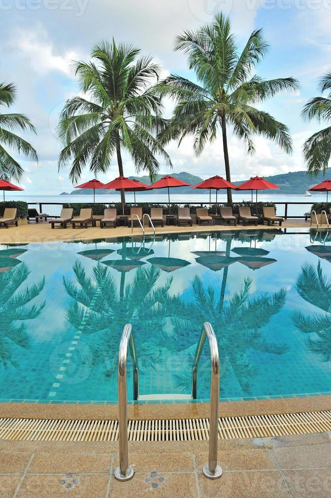 Lounge chairs and umbrellas poolside at a tropical resort photo