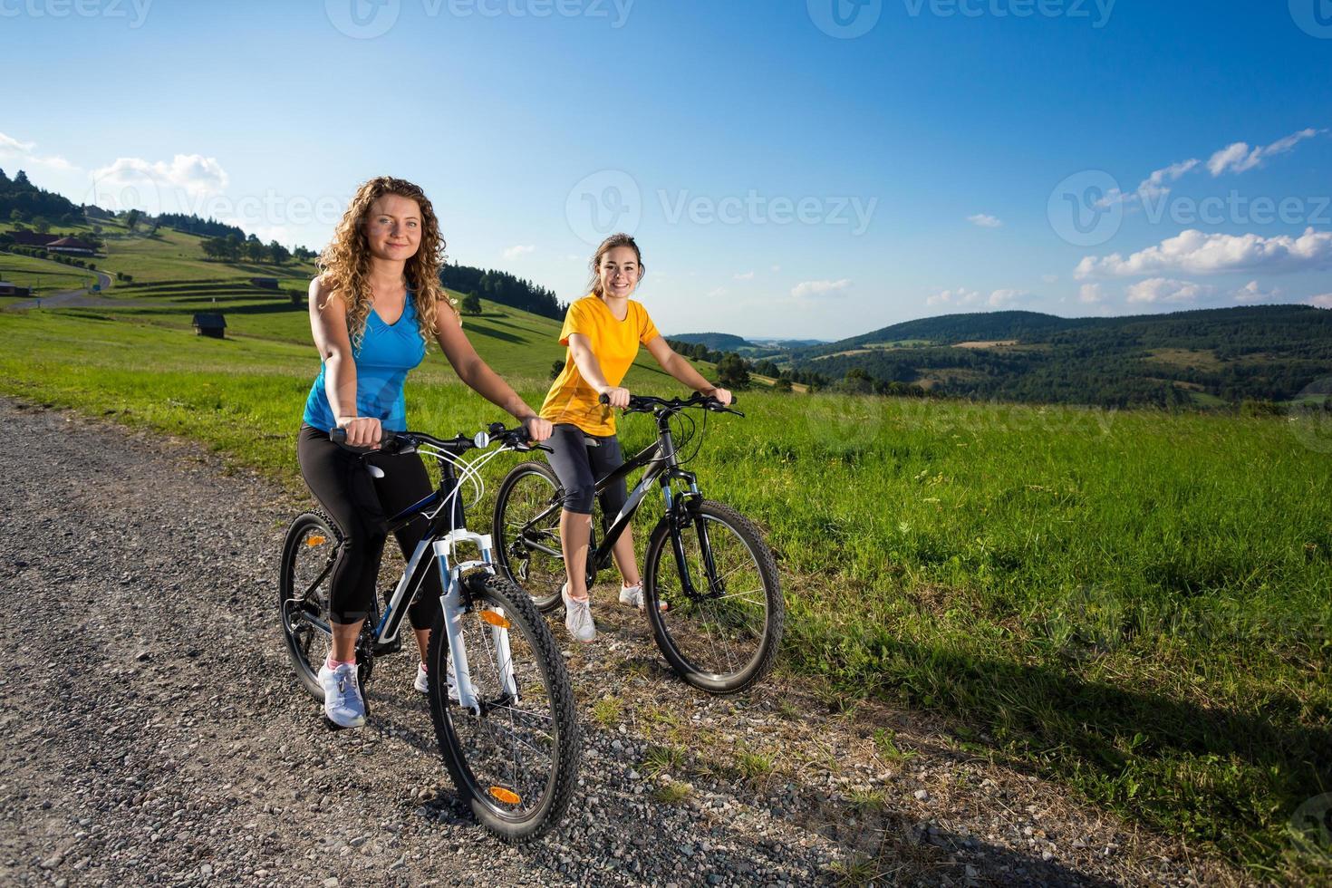 Two women riding bike photo