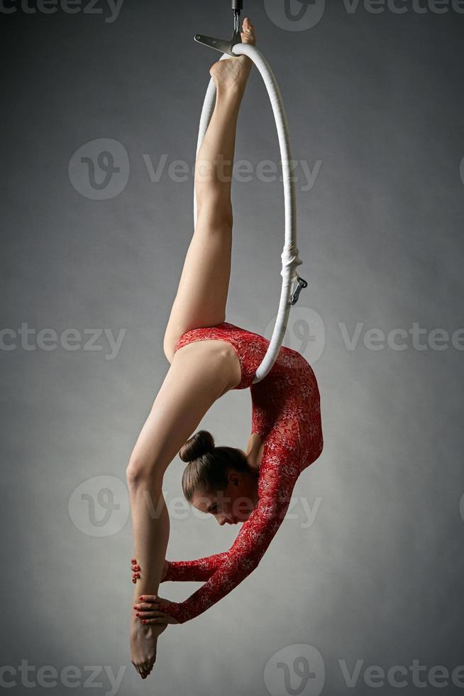elegante acróbata realiza truco gimnástico en el aro foto