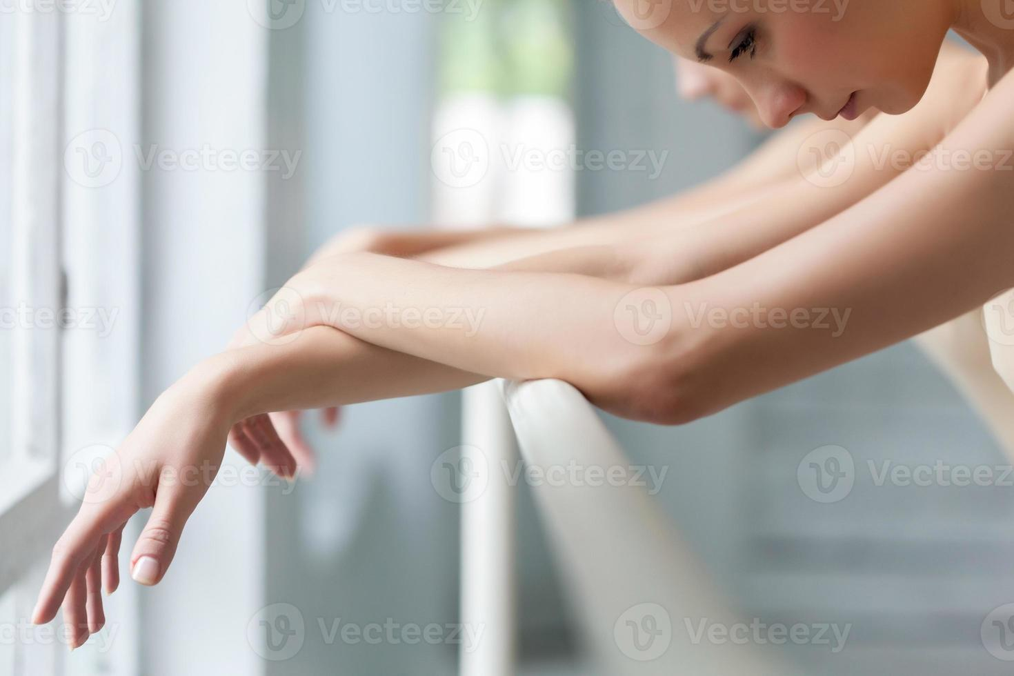 The  hands of two classic ballet dancers at barre photo