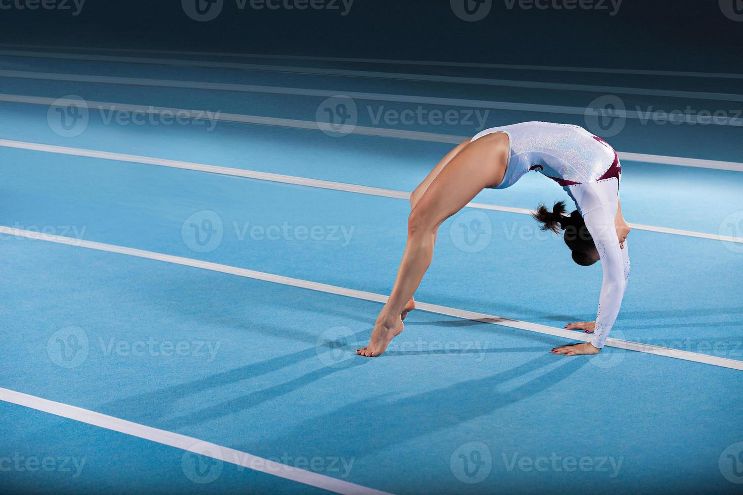 A young female gymnast posing in a bridge on a blue mat photo