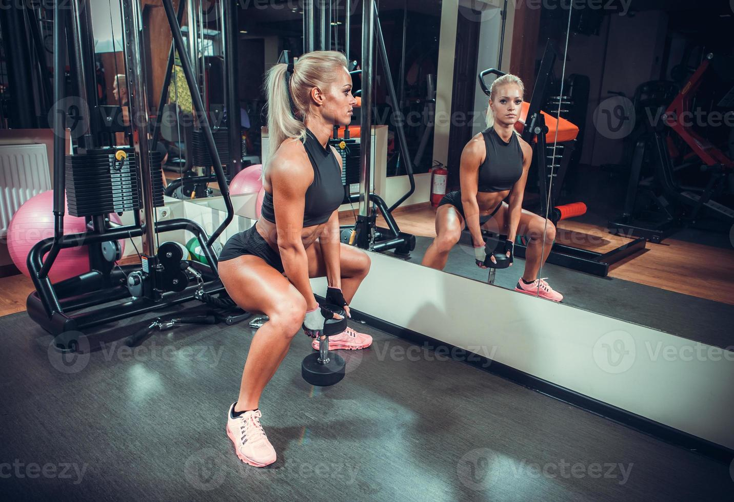 beautiful woman working out with a dumbbells in a gym photo