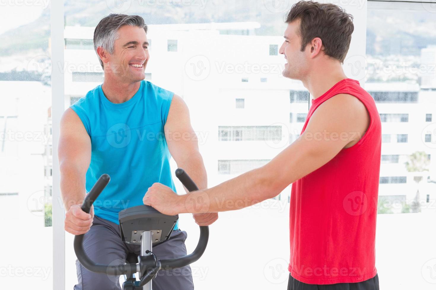entrenador con hombre en bicicleta estática foto