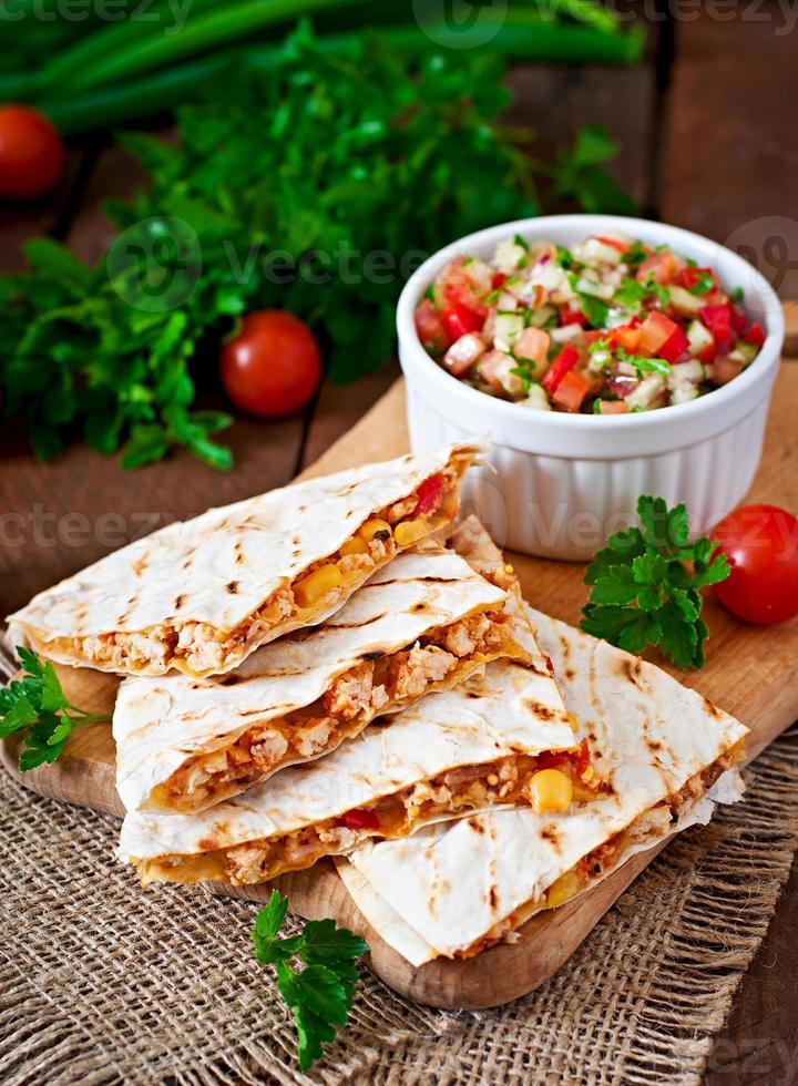 quesadilla mexicana envuelta con pollo, maíz y salsa foto