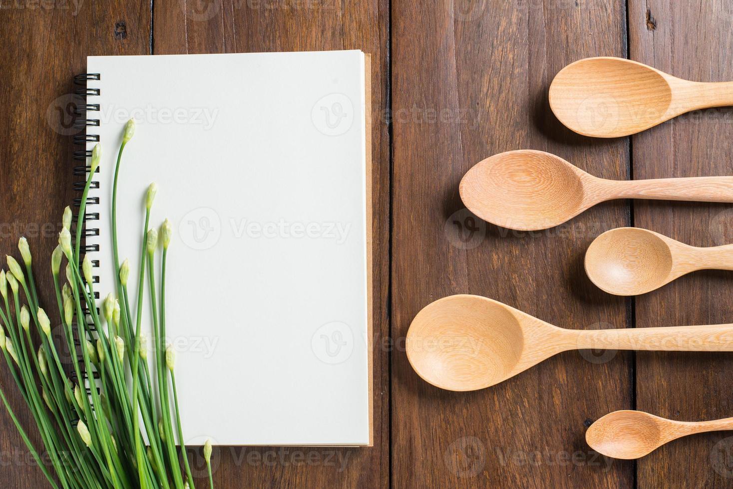 cuaderno de recetas, cuchara, tenedor sobre fondo de madera foto