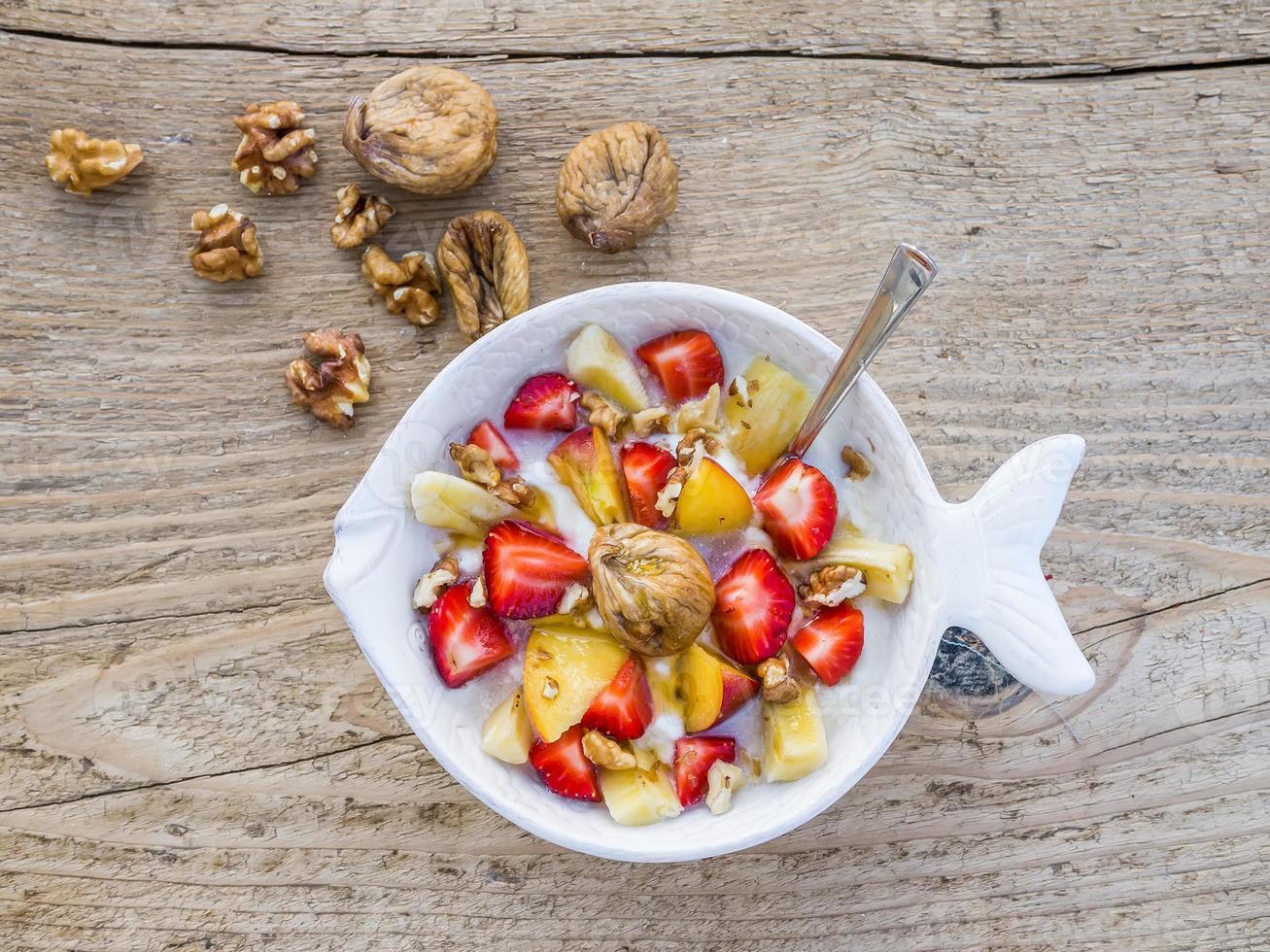 Bowl of fruit, walnuts and yogurt photo