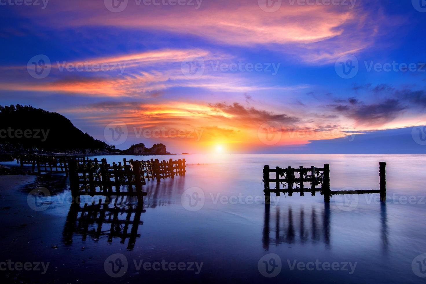 paisaje marino con hilera de madera al atardecer foto